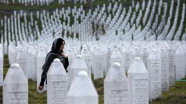 Une femme marche parmi les pierres tombales au Centre Potocari, près de Srebrenica.