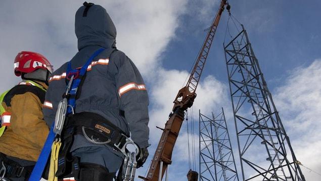 Des employés de SSi Canada devant des installations de télécommunications.
