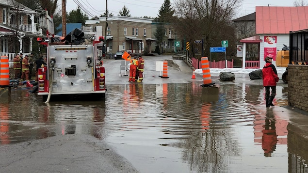 Un camion de pompiers est stationné dans l'eau, alors que des pompiers sécurisent les lieux.