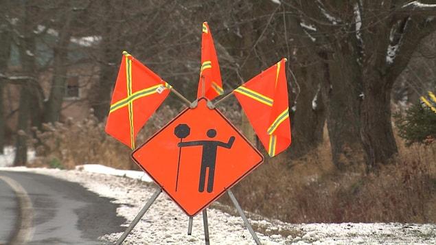 Un panneau de signalisation affichant qu'un signaleur de chantier est au travail.