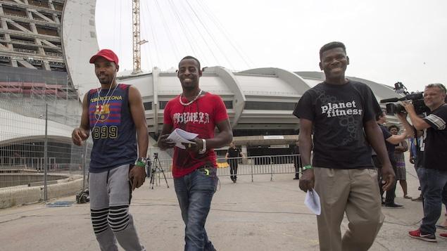 Trois hommes souriant sortent du stade olympique.