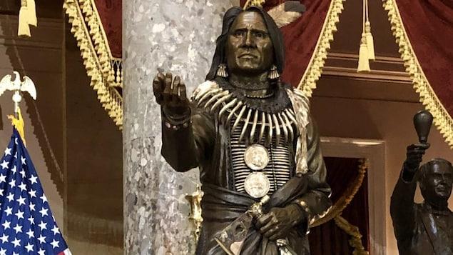 La statue du chef Standing Bear, en tenue de cérémonie, une main tendue et une hache dans l'autre, à côté du drapeau des États-Unis, dans le grand Hall des statues du Congrès américain.