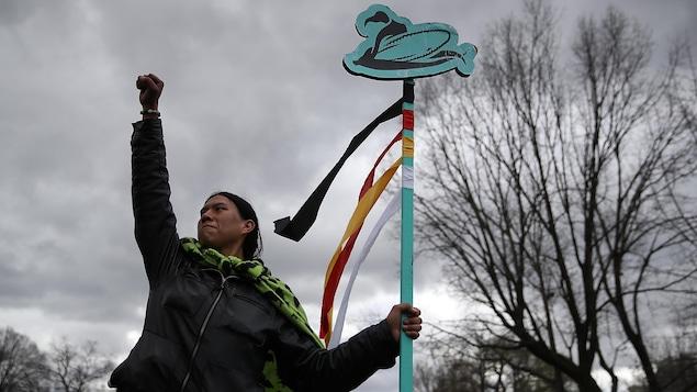 Un homme autochtone lève le poing dans les airs lors d'une manifestation.