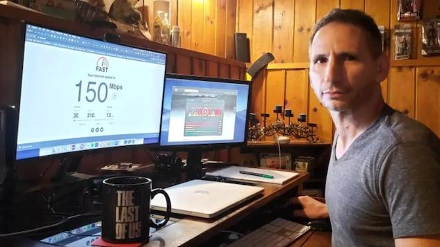 Un homme installé à son bureau à la maison devant un écran d'ordinateur qui affiche 150 Mbps.