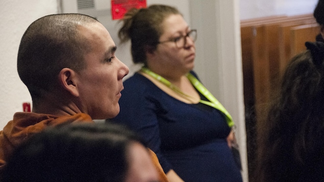 Un homme et une femme autochtone écoutent un conférencier.
