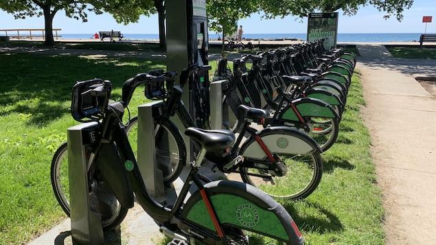 Des vélos de location alignés à une station près du lac Ontario.