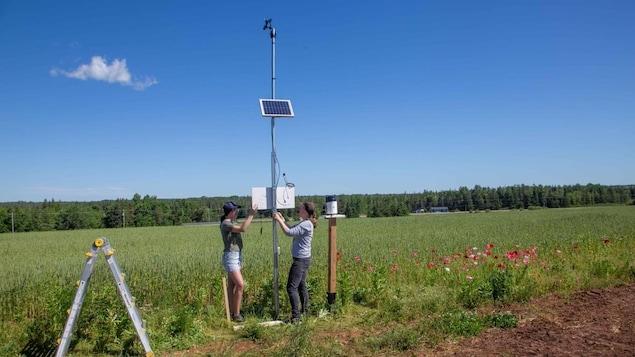 Deux chercheuses installent une station météorologique.