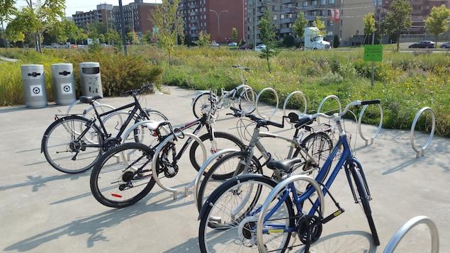 Des supports à vélos, des bacs à recyclage et une pancarte indiquant «milieu préservé pour la biodiversité».
