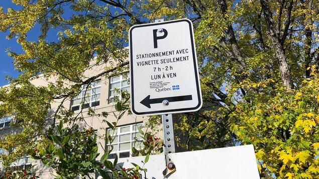 Un panneau indique « Stationnement avec vignette seulement, 7 heures-2 heures, lundi à vendredi, Centre intégré de santé et de services sociaux de l'Abitibi-Témiscamingue ».