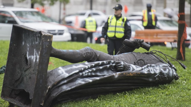 Des policiers montent la garde à côté de la statue, couchée de tout son long.