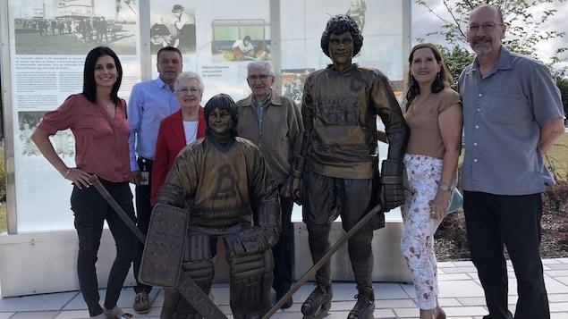 Manon Rhéaume, Patrick Dom et la famille de Sylvain Côté entourent la statue de bronze en hommage au tournoi peewee.