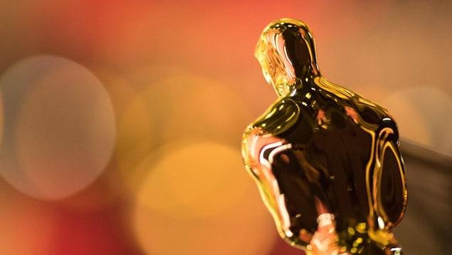 La statuette dorée des Oscars, de dos, dans une lumière orangée