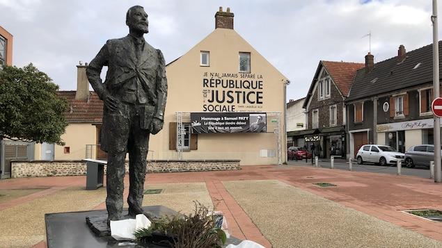 Des gerbes de fleurs ont été déposées au pied de la statue. derrière, une banderole à la mémoire de l'enseignant décapité Samuel Paty.