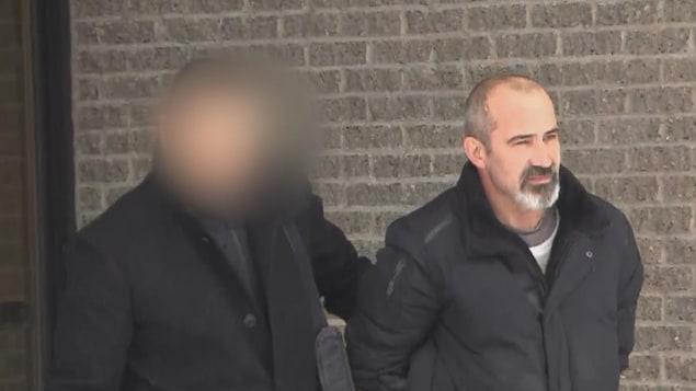Un homme est escorté par un policier.