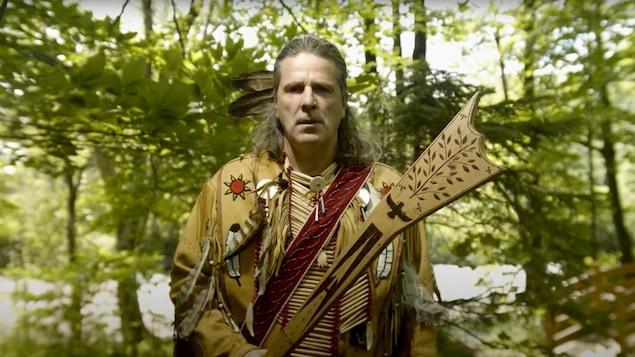 Un homme en habit traditionnel huron-wendat dans une forêt.