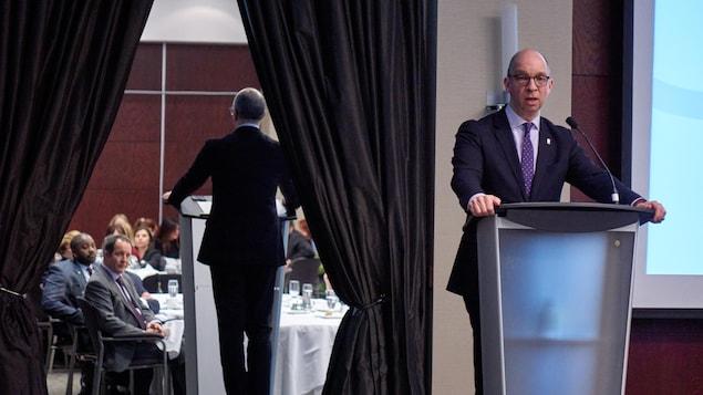 Le président de la Fédération des chambres de commerce du Québec, Stéphane Forget, faisant un discours devant des personnes assises autour de tables.