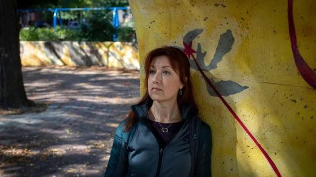 Une femme est adossée à un mur, dehors.