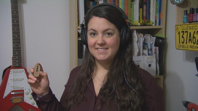 La jeune inventrice tient fièrement son produit, le E9 audio.