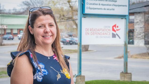 Stéphanie Patry pose pour une photo, à l'extérieur. Derrière elle se trouve une affiche du Centre de réadaptation en dépendance de l'Outaouais.