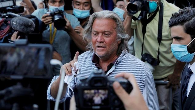 Steve Bannon, un masque à la main, au milieu de plusieurs journalistes et photographes.