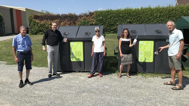5 personnes devant 2 bennes de verres
