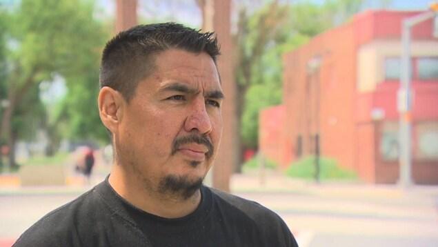 Un homme autochtone de 40 ans à l'extérieur debout.