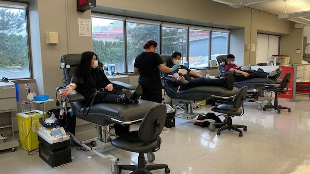 Trois personnes donnent du sang dans une clinique de la Société canadienne du sang.