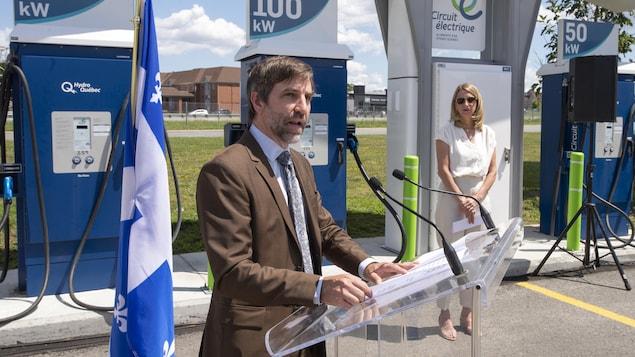 Le ministre du Patrimoine Steven Guilbeault en conférence de presse devant des bornes de recharge du stationnement du Cosmodôme de Laval.