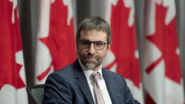Steven Guilbeault en gros plan devant une rangée de drapeaux canadiens.