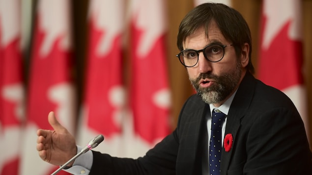 Steven Guilbeault parle dans un micro. Derrière lui sont installés plusieurs drapeaux canadiens.