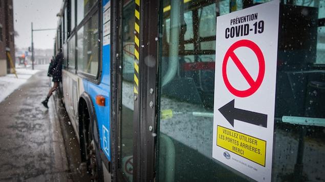 Une affiche sur laquelle il est écrit : prévention COVID-19, veuillez utiliser les portes arrières, merci