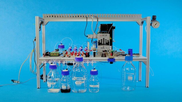 Une photo montrant un dispositif contenant des pièces électroniques branchées à un complexe système de bouteilles contenant des produits chimiques.