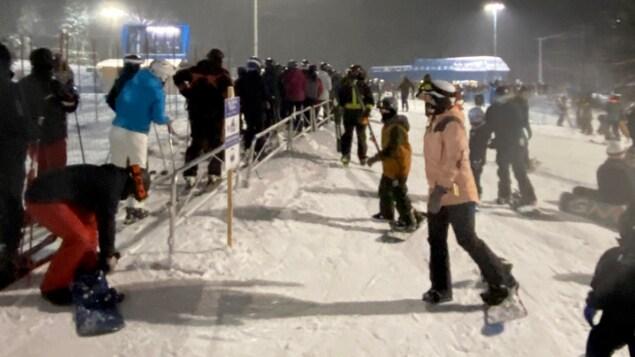 Plusieurs skieurs et planchistes en attente pour utiliser la remontée mécanique un soir d'hiver