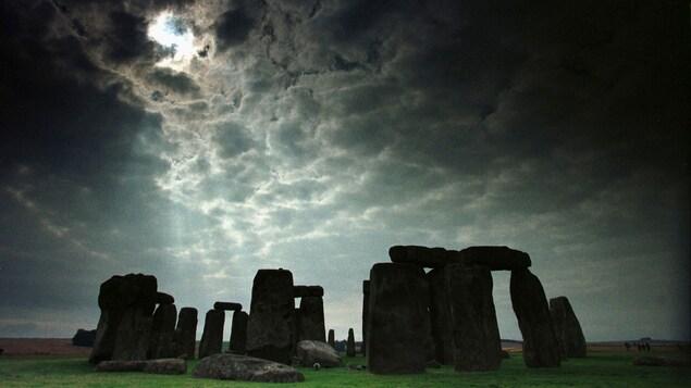 On voit le monument de pierres dressées de Stonehenge, sous un ciel nuageux.