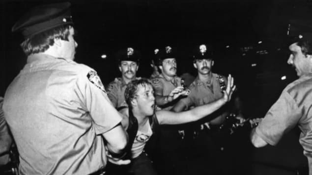 Un homme est entouré de policier.