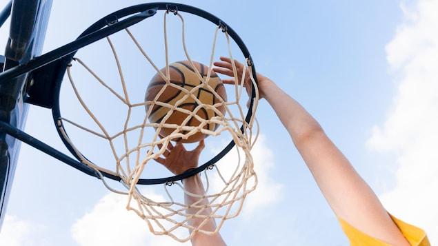 Une personne tient un ballon de basket et le lance dans un panier.
