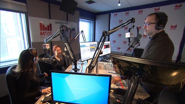 Un studio de radio avec trois animateurs.
