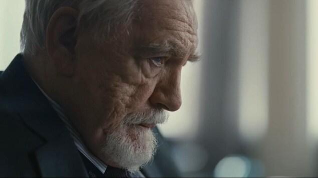 Un homme âgé en complet affiche un air inquiet.
