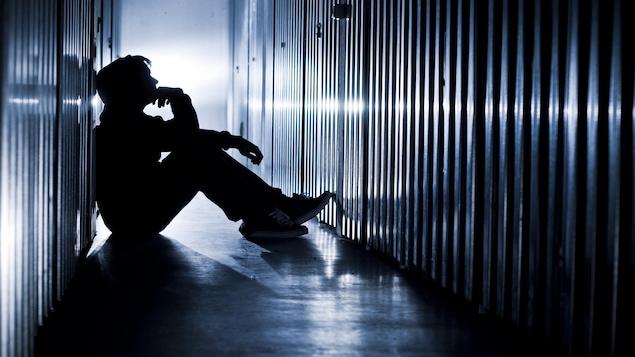 Un adolescent est assis sur le sol dans la pénombre dans un corridor.