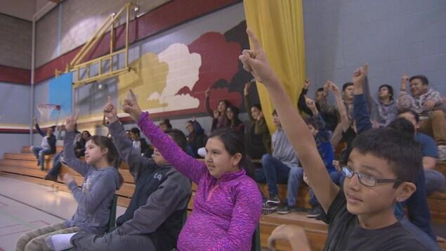 Des jeunes lèvent la main.