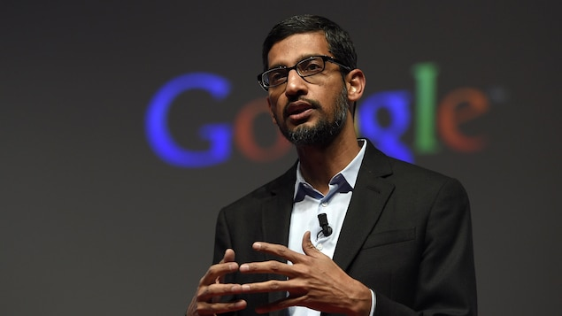 Le PDG de Google et d'Alphabet Sundar Pichai parle sur une scène devant le logo de Google.