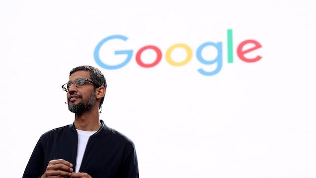 Le PDG de Google Sundar Pichai parle à une foule devant un écran orné du logo de Google.