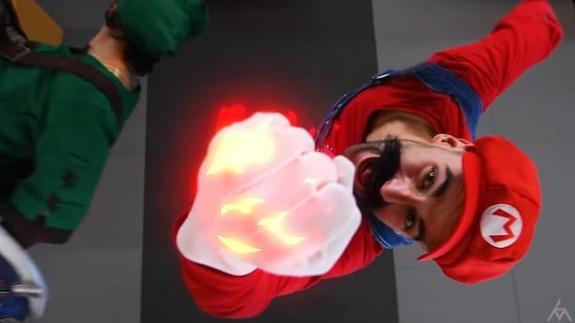 Une capture d'écran de la vidéo montrant un homme déguisé en Super Mario, avec sa salopette bleue, son chandail et sa casquette rouge et sa moustache, en train de brandir son poing en feu devant la caméra.