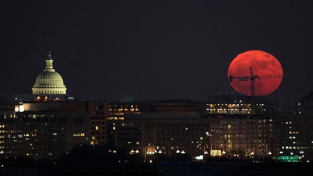 Une super lune apparaît dans un ciel nocturne de la capitale américaine, Washington, avec le Capitole en périphérie.