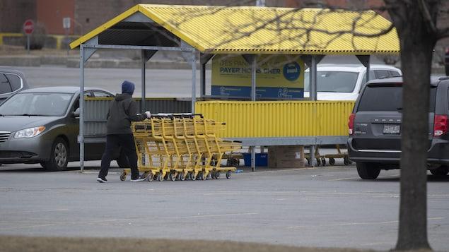 Un commis avec des chariots d'épicerie chez Maxi.