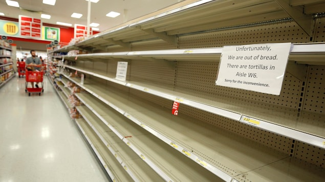 Dans ce supermarché de Kissimmee, en Floride, les clients se heurtent à des étagères vides en raison des provisions que se sont faites de nombreux résidents. Des scènes similaires se déroulent à de très nombreux endroits.