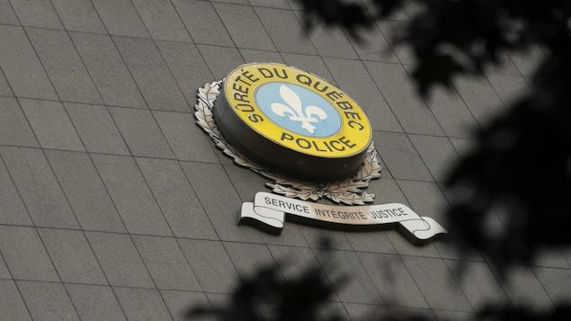 Une vue en contre-plongée du bâtiment de la SQ avec le logo de l'organisation. On voit en premier plan des branches d'arbres.