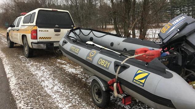 Un véhicule de la SQ transportant un zodiac, stationné en bordure d'une route.
