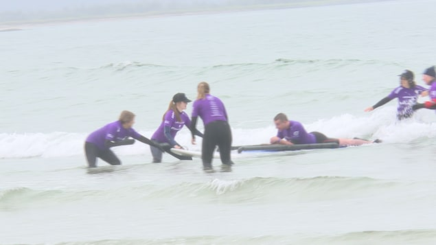 Des bénévoles aident un homme faisant du surf couché sur sa planche