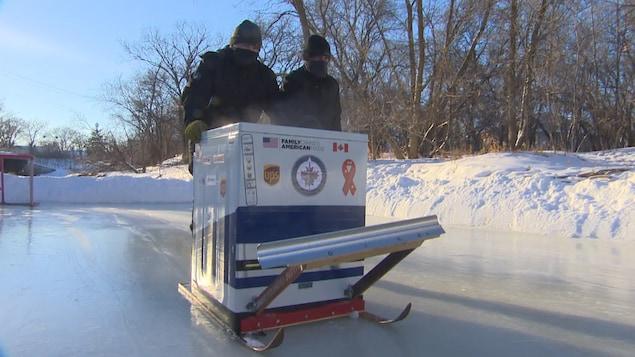 Anthony Theriault et Ron Theriault sont debout derrière la laveuse qui avance sur la patinoire.